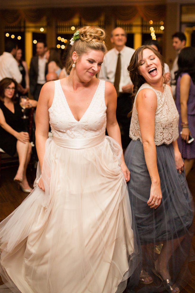 bride in bhldn wedding dress dancing with maid of honor in bhldn crop top bridesmaid dress
