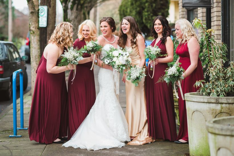 Bridal party laughing with bride in red dresses and bouquets