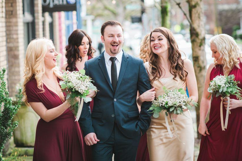groom walking with bridesmaids