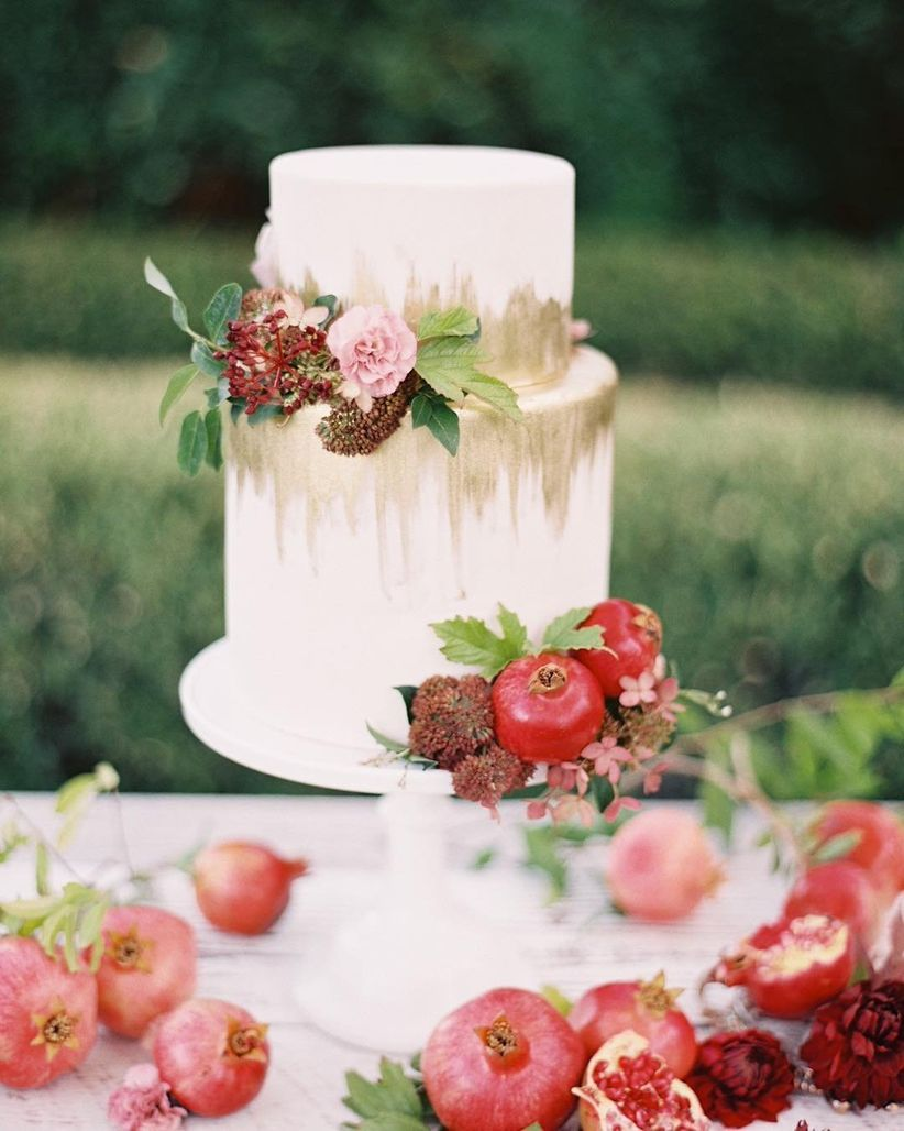 white fondant cake with gold ombre accents and fresh flowers with pomegranates