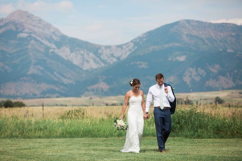bride and groom walk through green meadow in montana at outdoor wedding with mountain peaks in the background