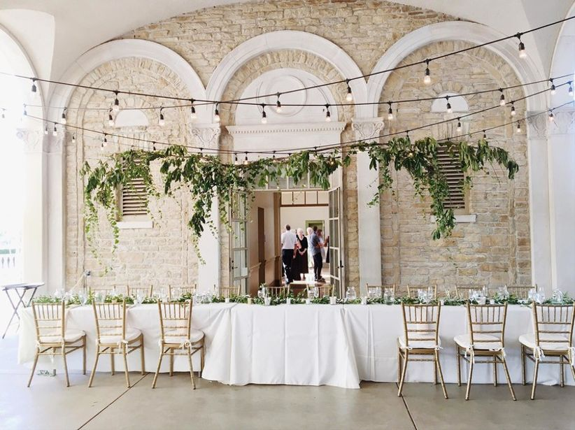 romantic woodland wedding idea — hanging greenery and string lights above main table