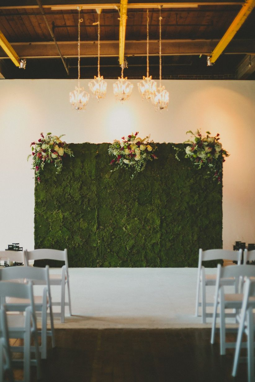 romantic indoor ceremony altar decoration idea with moss backdrop and flowers