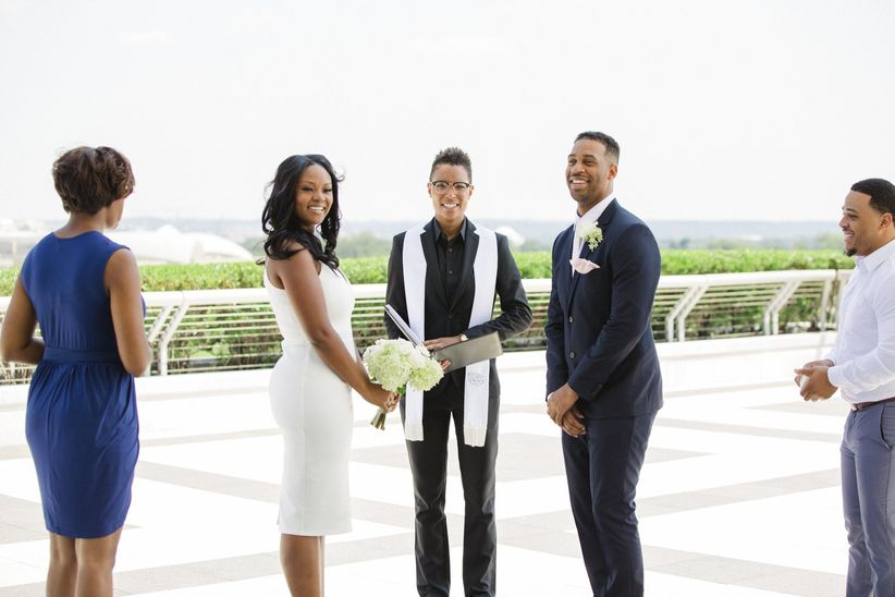 a bride and groom stand in front of an officiant at their wedding on the rooftop terrace of the kennedy center for performing arts
