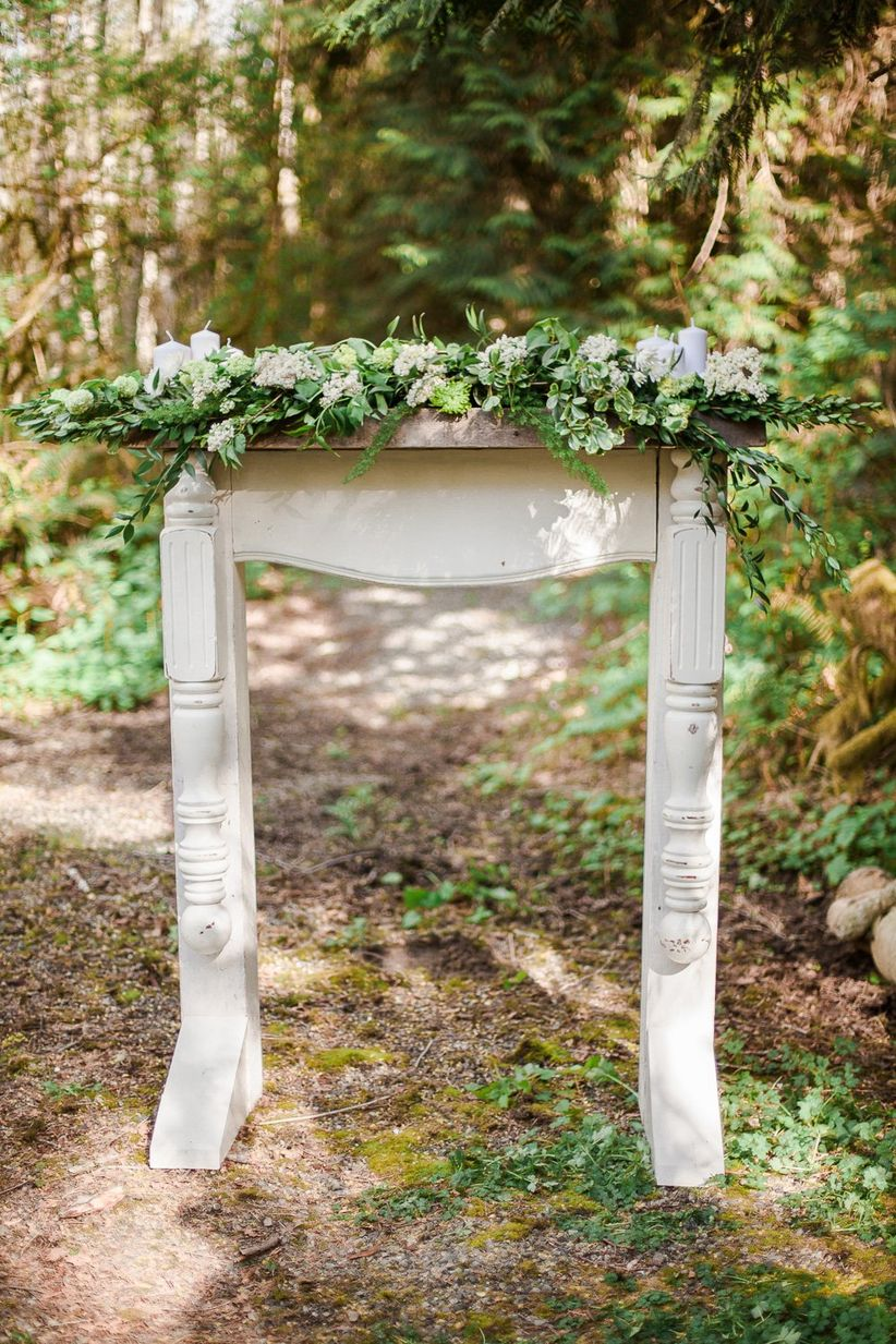 DIY ceremony backdrop with greenery and candles