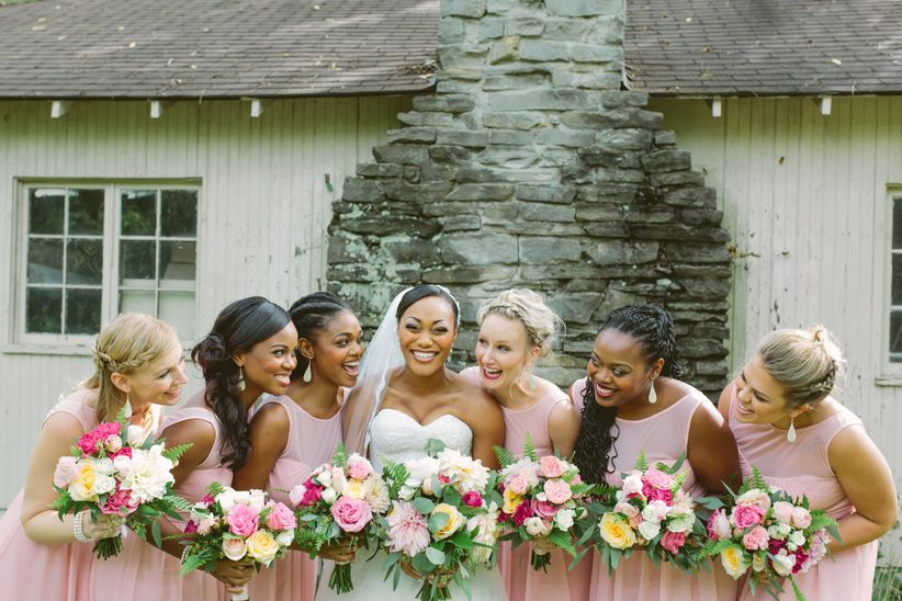 bridesmaids in pink carrying bouquets