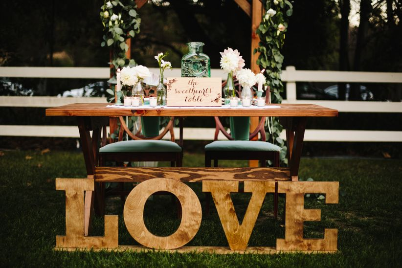 shabby chic rustic outdoor sweetheart table marquis letters floral arch