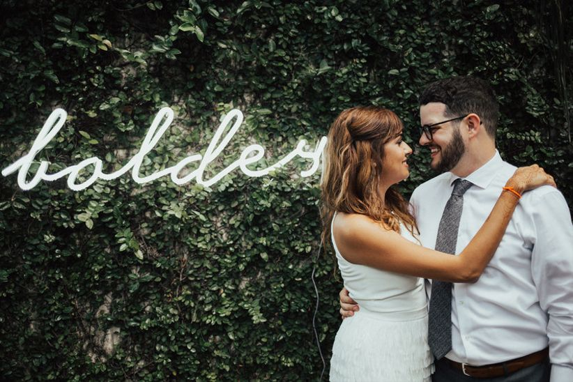 modern wedding backdrop idea with custom neon sign showing couple