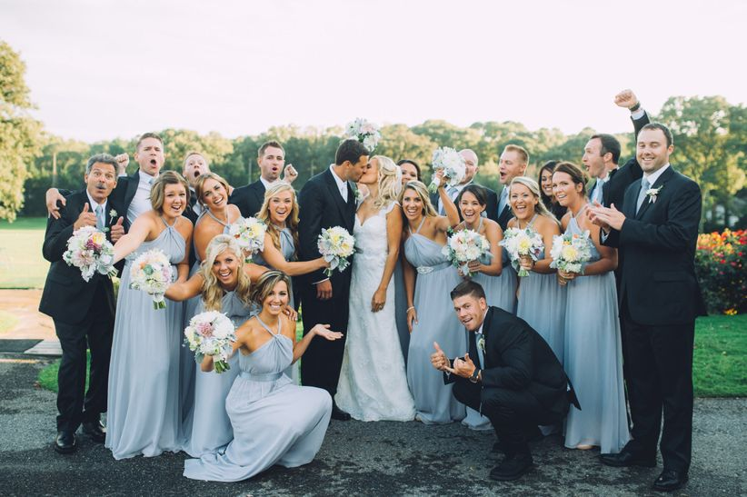The pros and cons of a big wedding party weddingwire cheering wedding party with couple kissing junglespirit Image collections