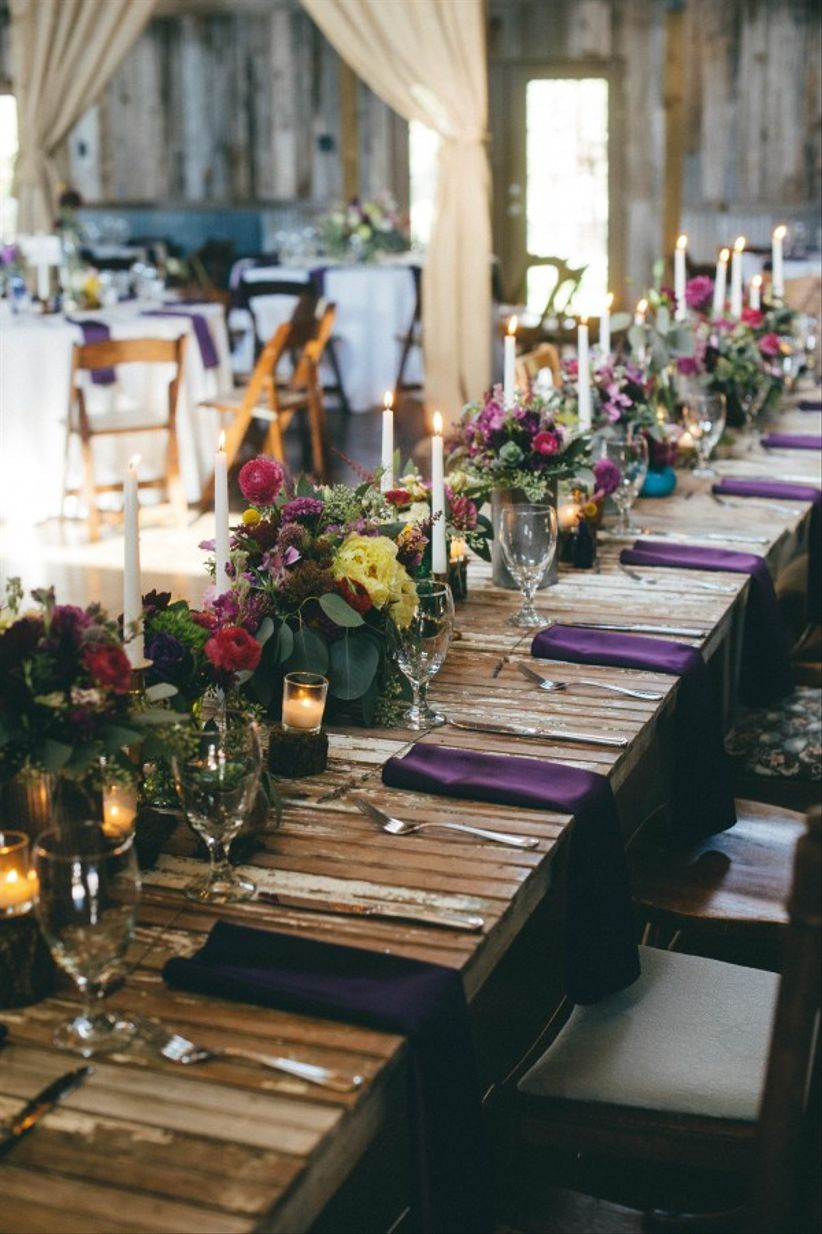 wooden table with green and purple centerpiece, tall candles, purple napkins