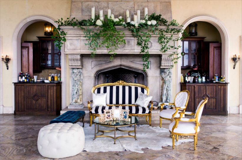 modern wedding lounge area in front of a stone fireplace decorated with greenery garland and white taper candles