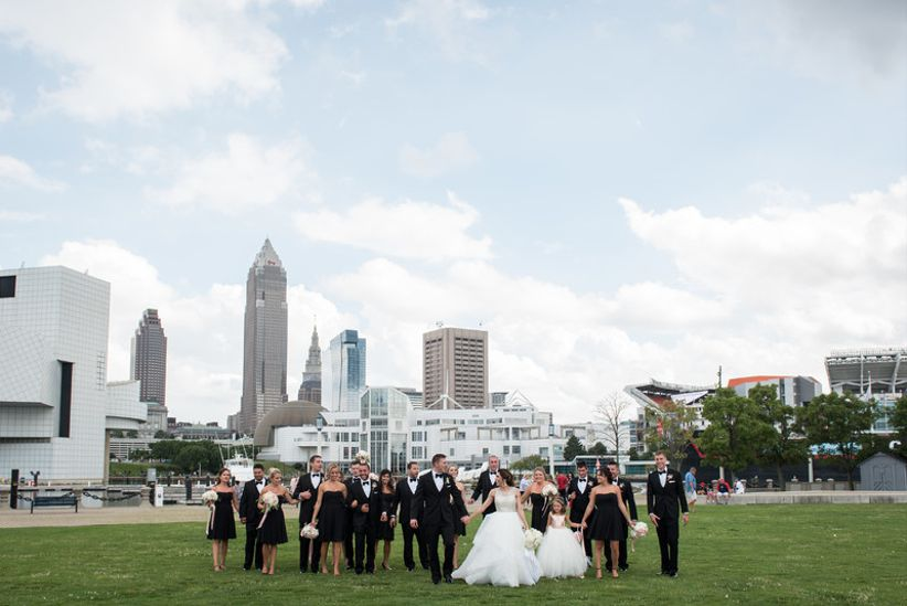 formal wedding party poses in a park in downtown cleveland with skyline in the background