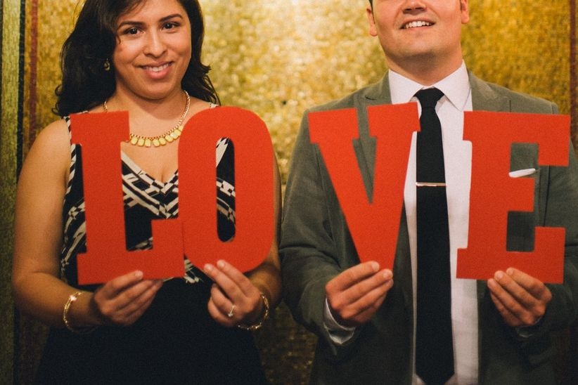 couple holding love sign engagement photo