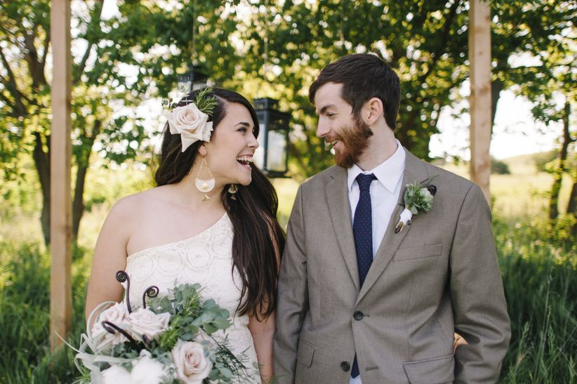 Boho rustic couple bride in asymmetric lace gown groom in brown suit laughing under outdoor altar