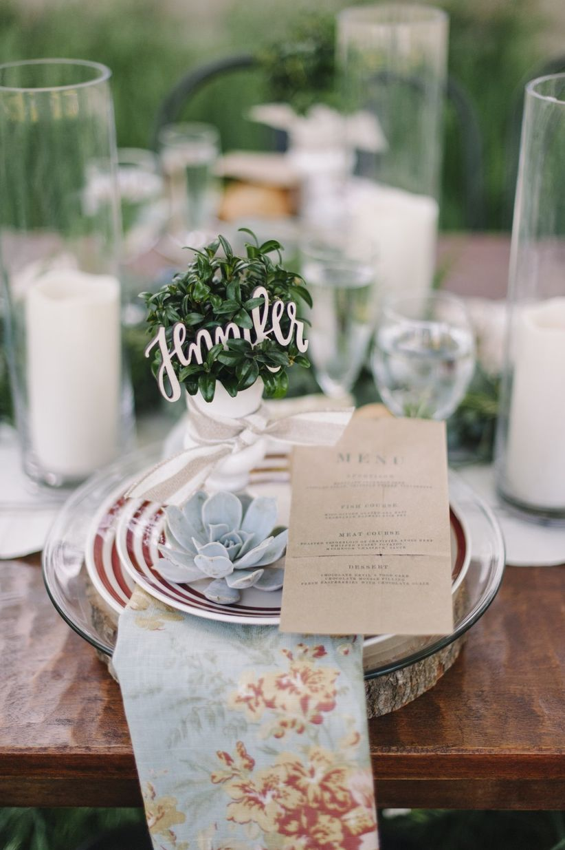 close up place setting gold laser cut place cards in greenery mismatched striped plates on wood slices votive candles