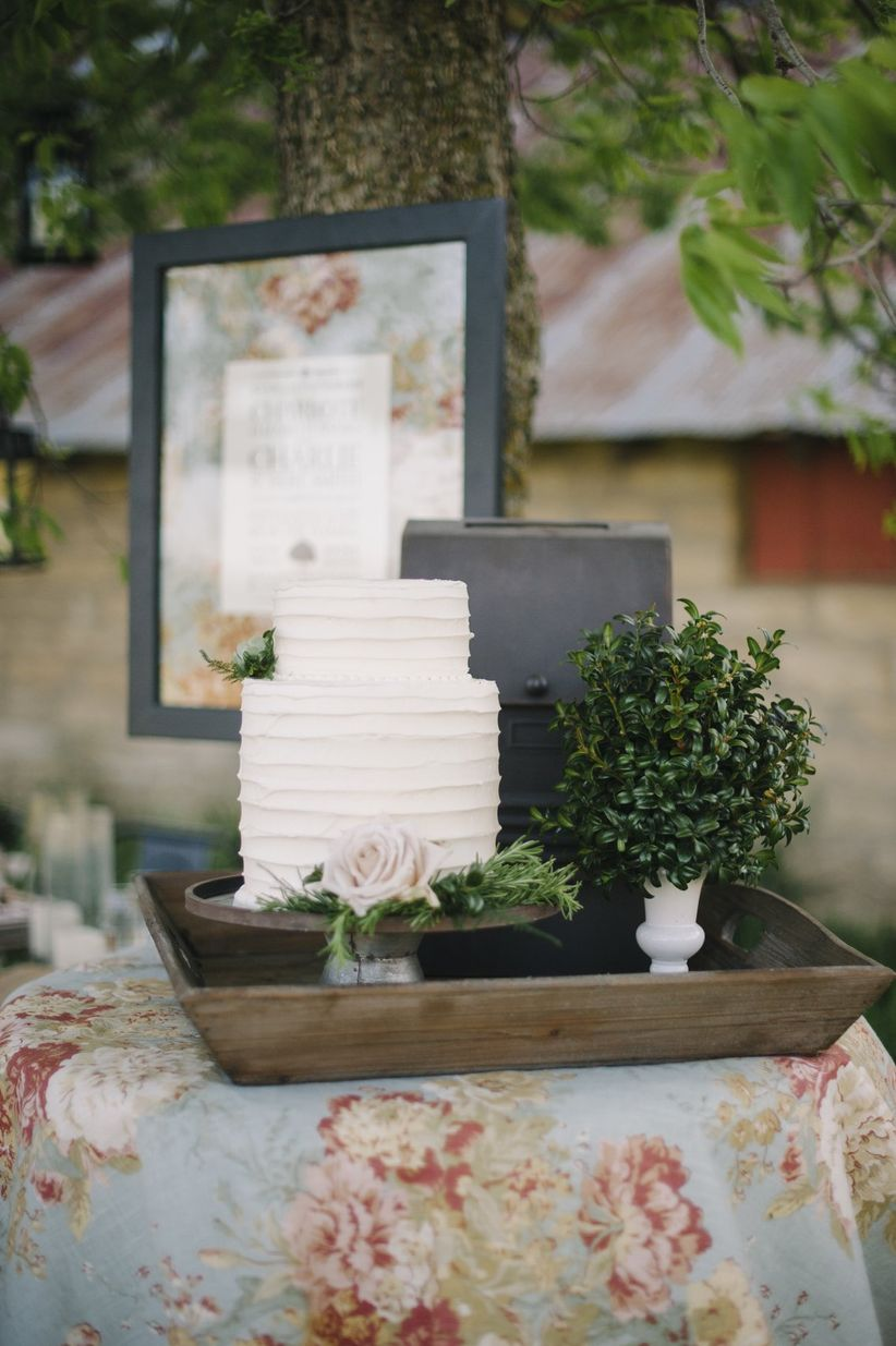 buttercream frosted cake on bronze stand on display outdoor with roses and greenery