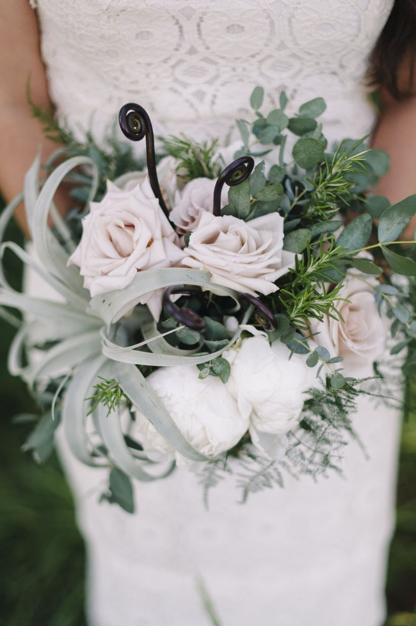 bride outdoor holding bouquet featuring peonies, roses, air plants, fiddlehead fern, and rosemary