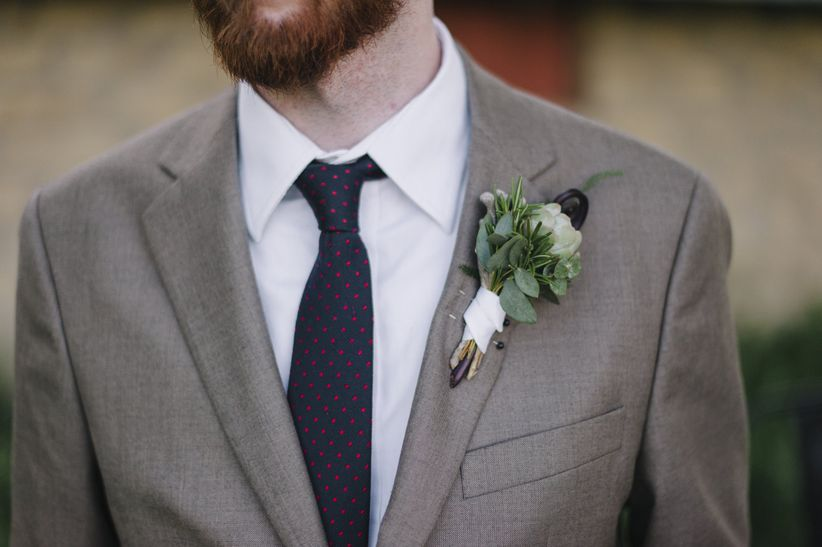 close up shot of groom in brown suit blue necktie with red polka dots boutonniere featuring succulent berries and greenery