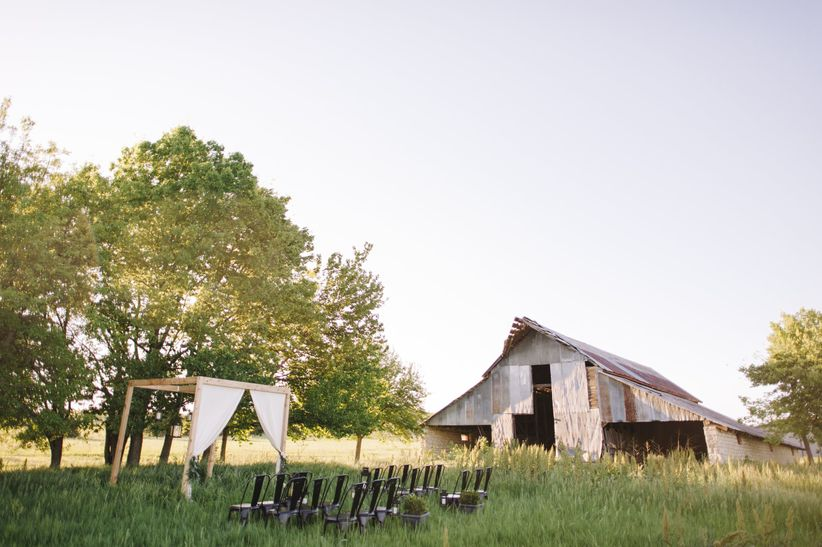 Outdoor ceremony site wooden arch with white linens and flowers black metal surrounded chairs tall grass