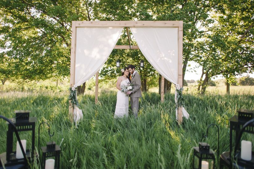 couple stand under arch decorated with flowers and white linens