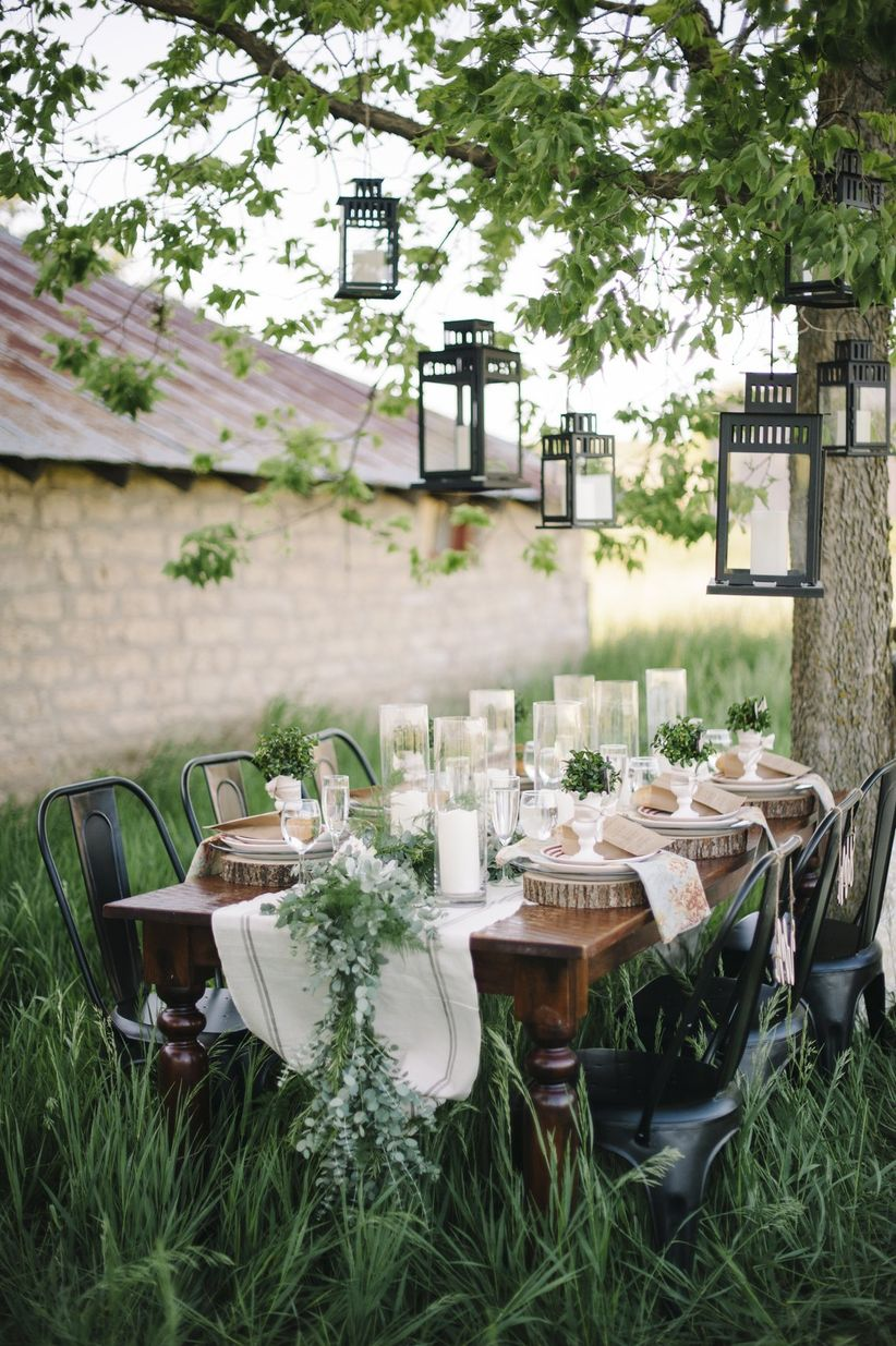 rustic vintage tablescape outdoor in tall grass black metal chairs linen table runner and greenery runner