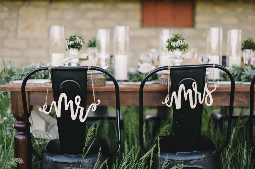 mr and mrs gold laser cut signs on black metal chairs