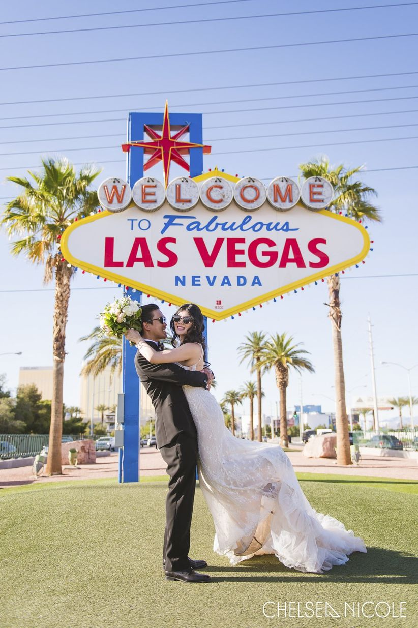 couple in front of welcome to las vegas sign