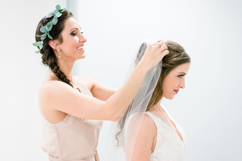 maid of honor helping with bride veil