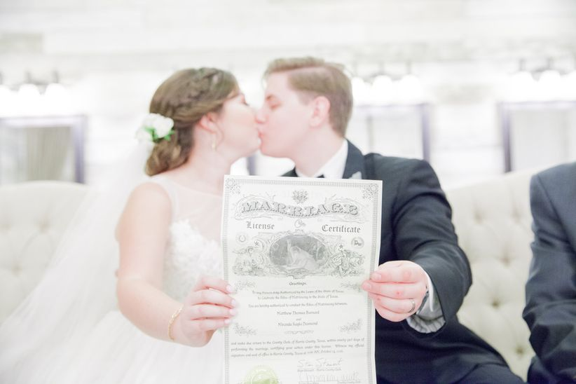 couple holding marriage license and kissing