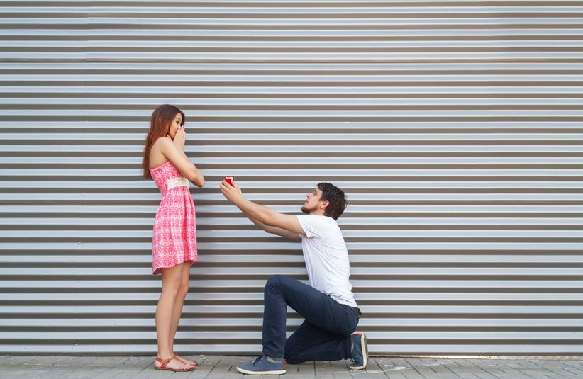 young couple proposing, man on one knee, woman in shock
