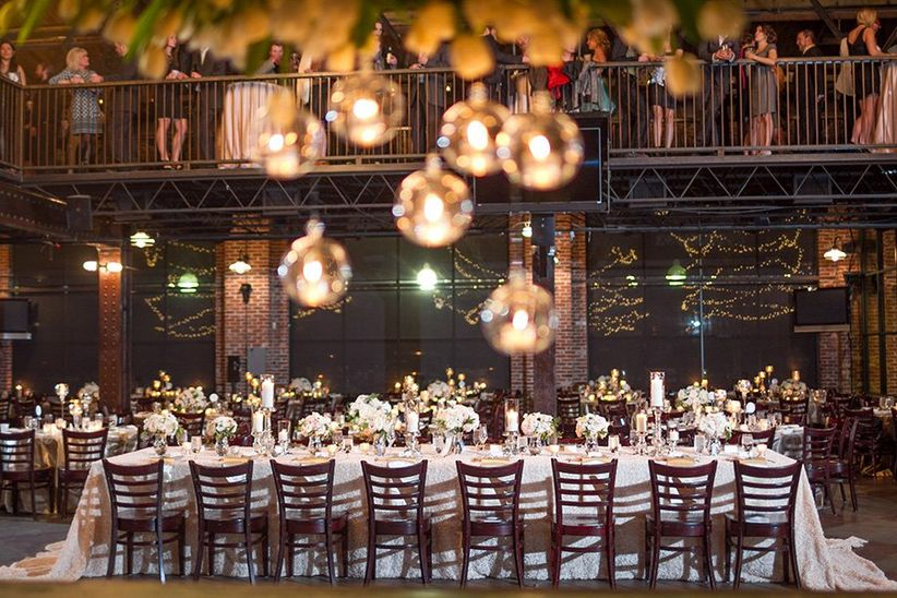 mile high station indoor reception rectangular banquet tables white linens hanging light bulbs