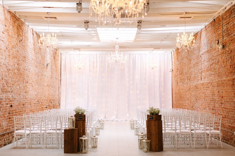 loft ceremony space string lights linen backdrop rustic white chiavari chairs aisle markers