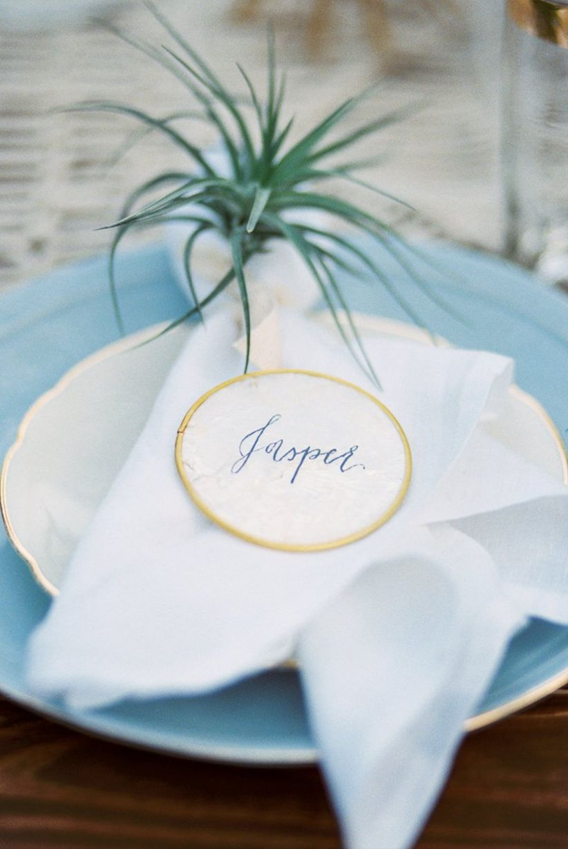 modern place setting with greenery and calligraphy place card
