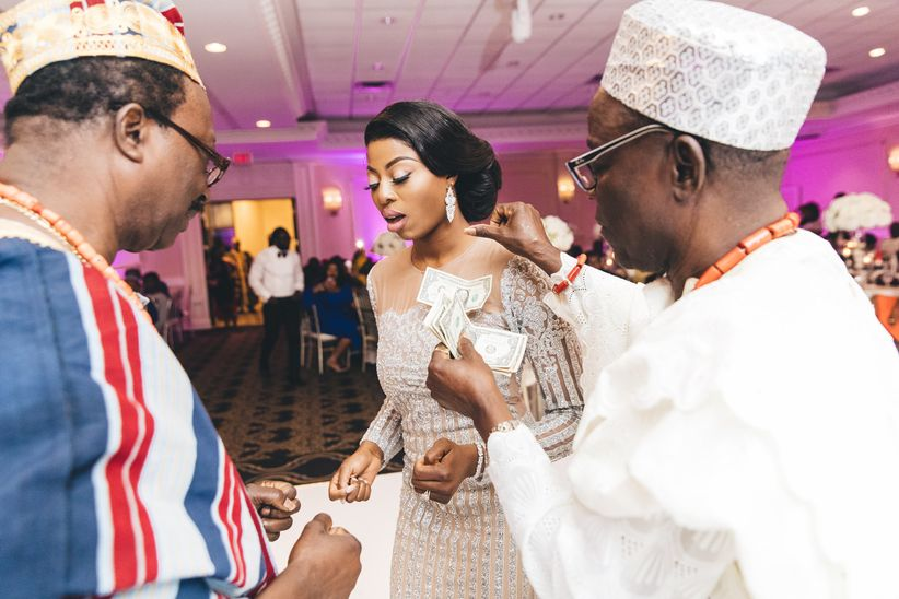 Nigerian bride in a jeweled gown on a wedding dance floor with two men in traditional Nigerian attire pin money to her.