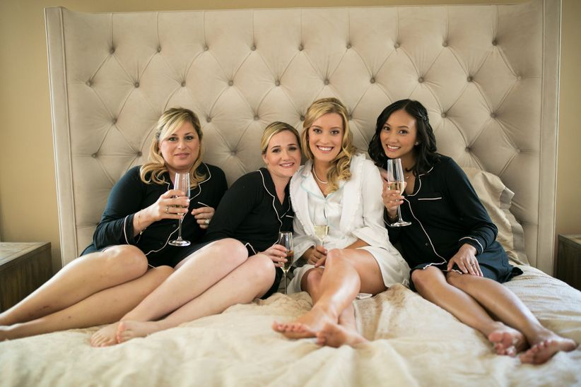 bride and bridesmaids in pajamas with champagne