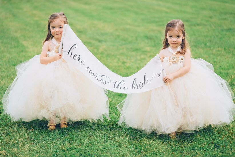 two flower girls carrying calligraphed sign