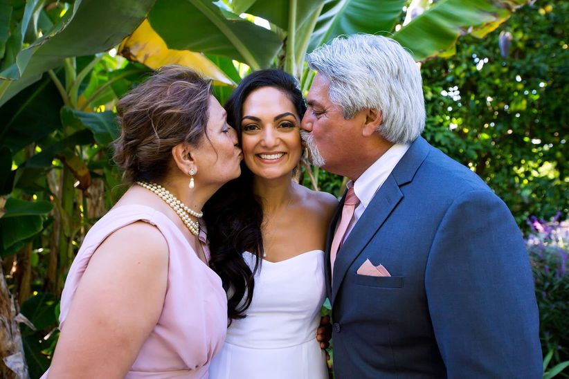 parents kissing bride