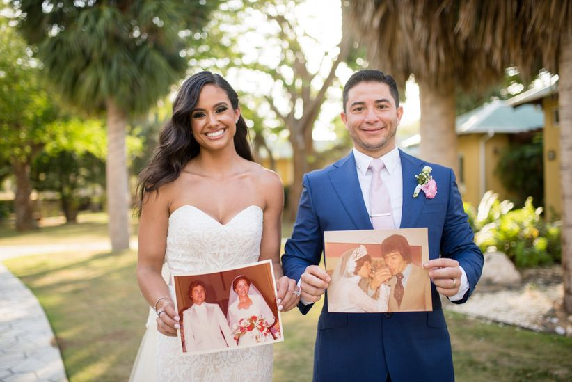 couple hold photos of their parents on their wedding day