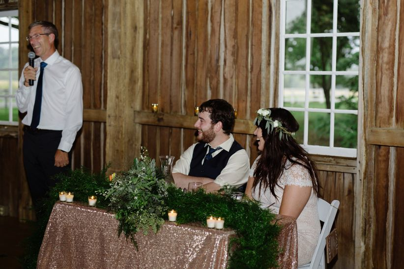 newlyweds smile as parent gives speech