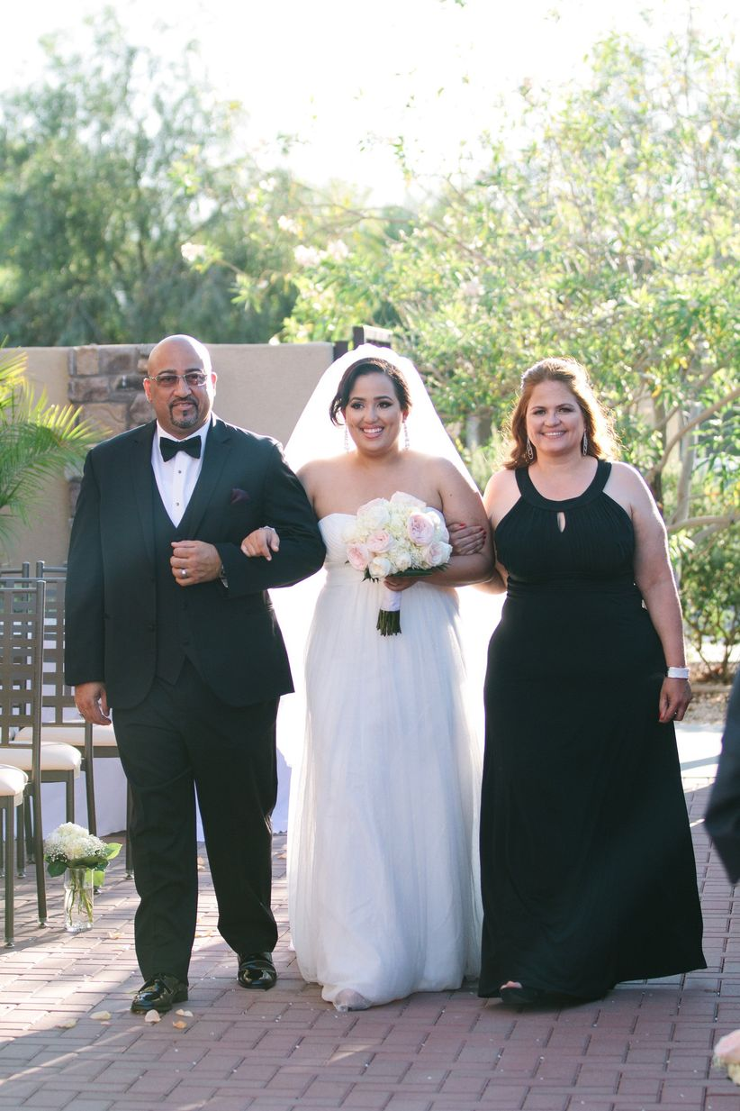 bride walks dow the aisle with both parents