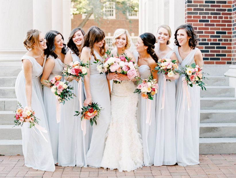 spring bridal party wearing long blue bridesmaid dresses with pink bouquets