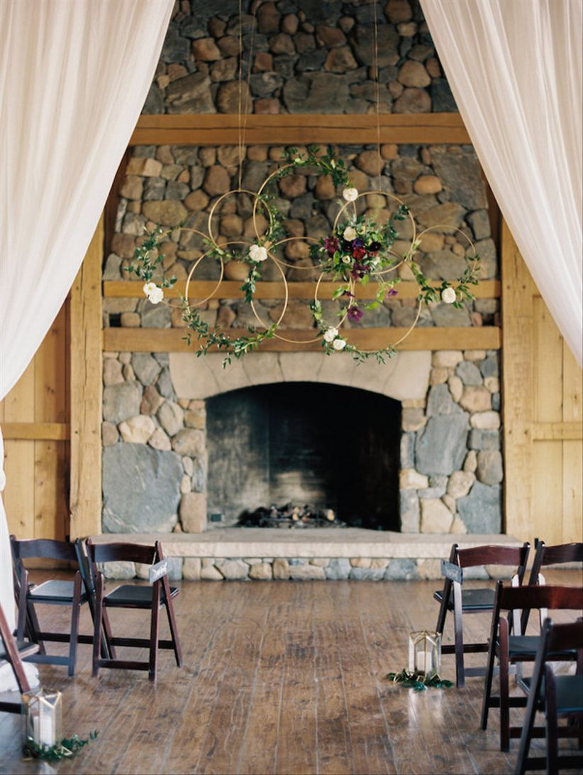 indoor wedding ceremony idea with floral wreath backdrop