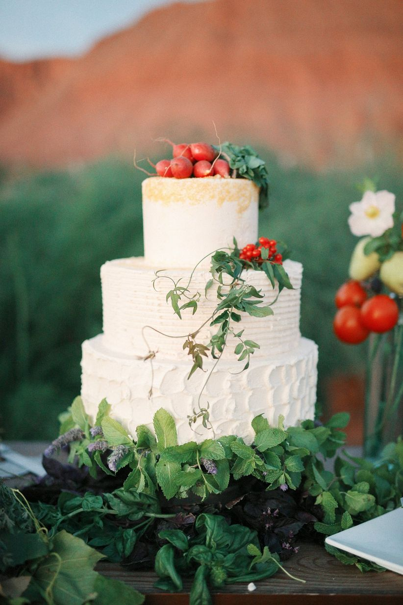buttercream wedding cake decorated with greenery