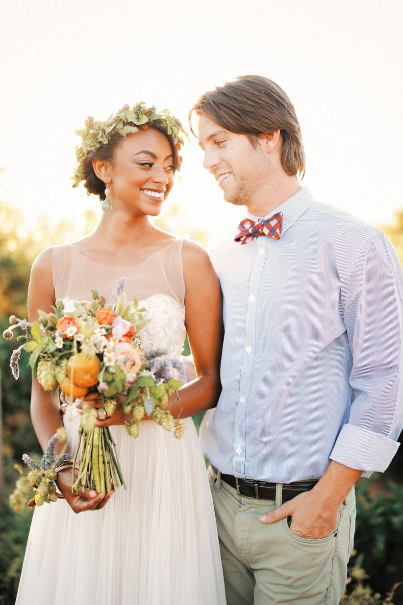 bride and groom posing in a garden at sunset