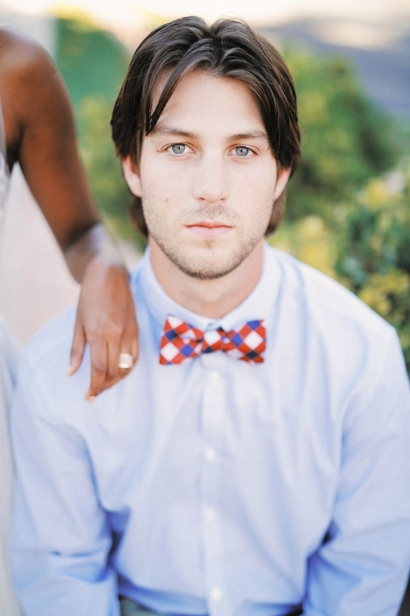 groom wearing red and blue plaid bow tie