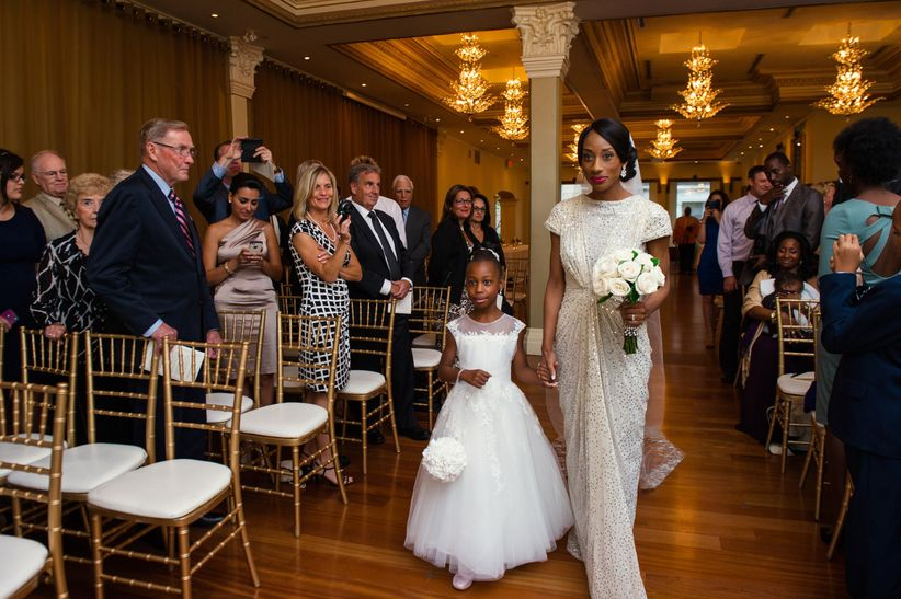 bride and daughter walking down aisle together