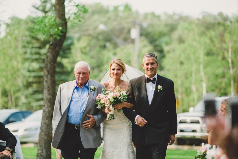 bride with father and stepfather walking down aisle