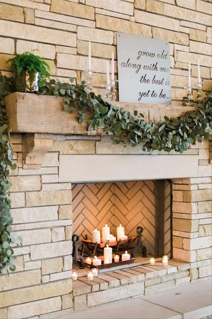 stone fireplace mantel at romantic wedding venue decorated with greenery garland and love quote sign