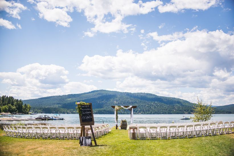 rows of chairs are set up in front of a lake for waterfront wedding ceremony