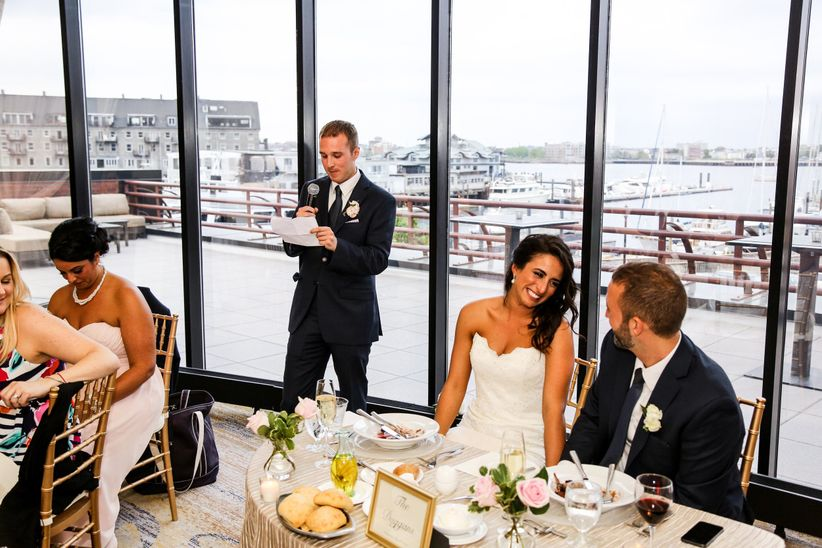 couple at reception table during best man speech